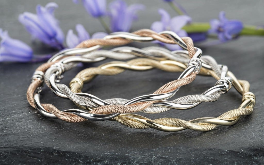 valentines day gift ideas 2019 three 9ct yellow gold 9ct white gold and 9ct rose gold bangles on a black slate with purple flowers in the background